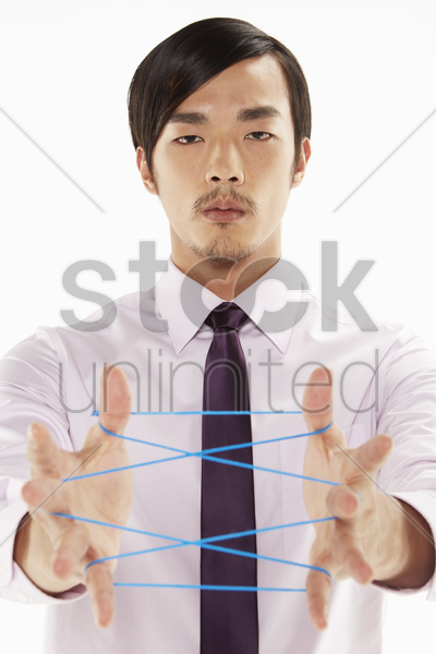 businessman forming a cat's cradle stock photo