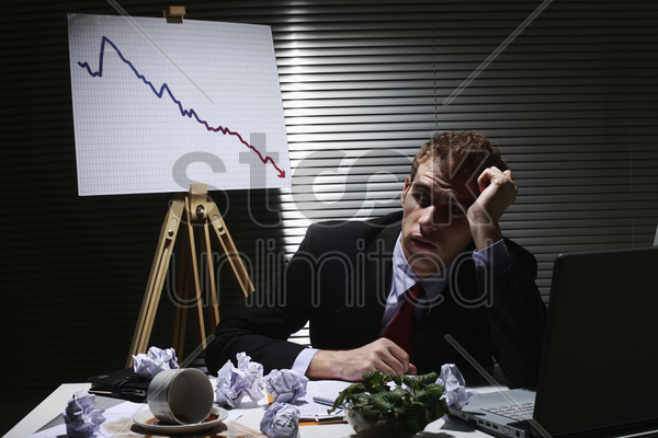 businessman frowning with crumpled paper balls on the table stock photo