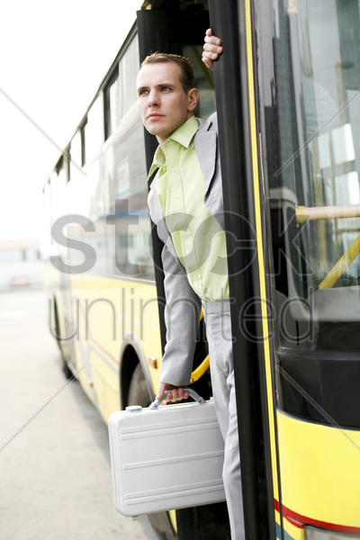 businessman getting down from a bus stock photo