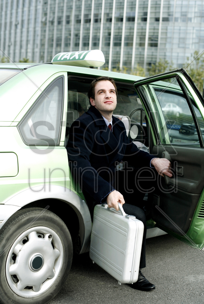 businessman getting out from a taxi stock photo