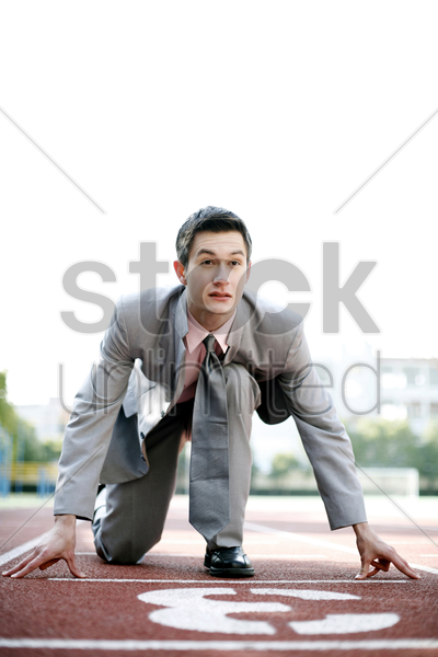 businessman getting ready on the running track stock photo