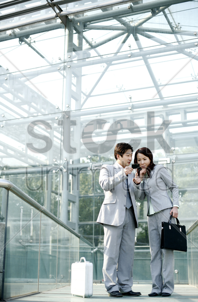 businessman giving his business card to a businesswoman stock photo