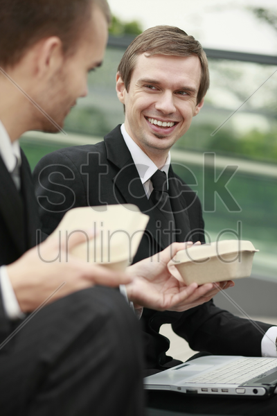businessman giving take out lunch to his colleague stock photo