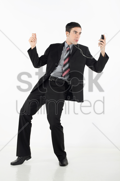 businessman grooving while listening to music on mp3 player stock photo