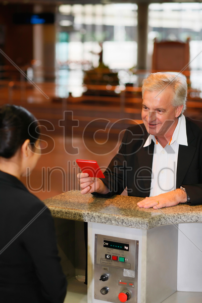 businessman handing airline check-in attendant his passport upon arrival stock photo