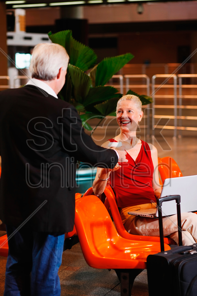 businessman handing businesswoman a cup of coffee stock photo