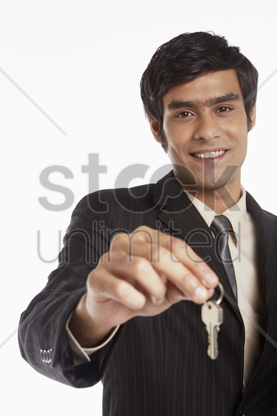 businessman handing out a set of keys stock photo