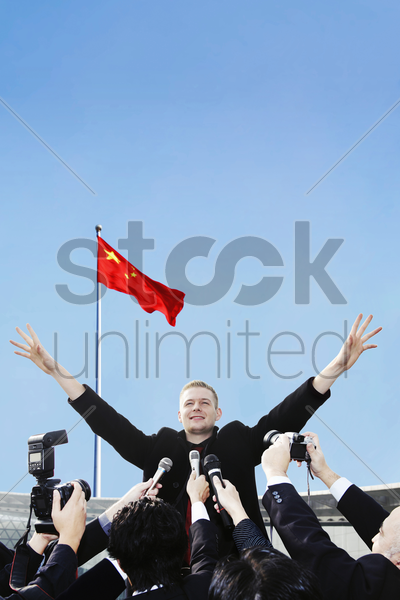 businessman handling a group of reporters stock photo