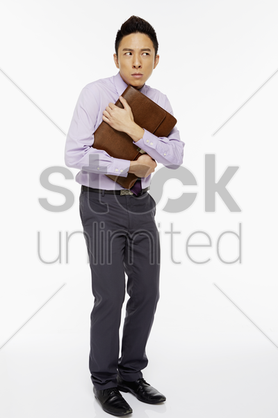 businessman hanging on tightly to his briefcase stock photo