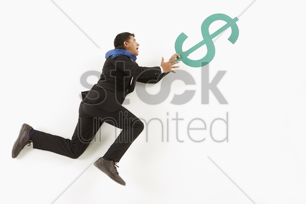 businessman hanging on to a dollar sign stock photo
