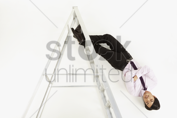 businessman hanging upside down stock photo