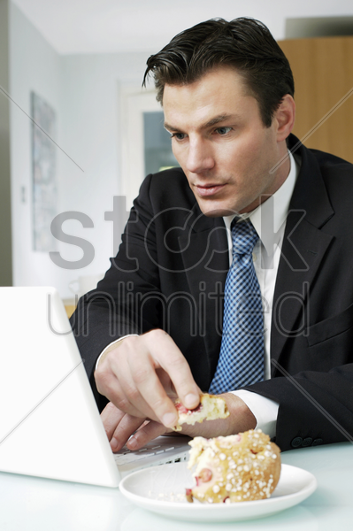 businessman having breakfast while using laptop stock photo