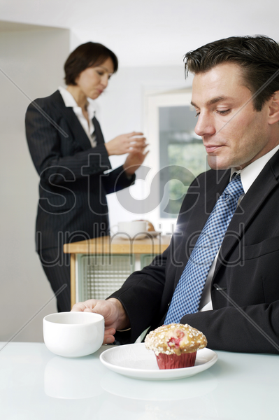 businessman having breakfast with wife standing in the background stock photo