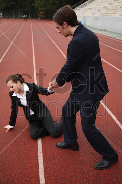 businessman helping fallen businesswoman stock photo