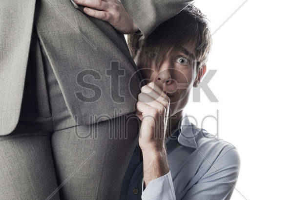 businessman hiding behind businesswoman stock photo