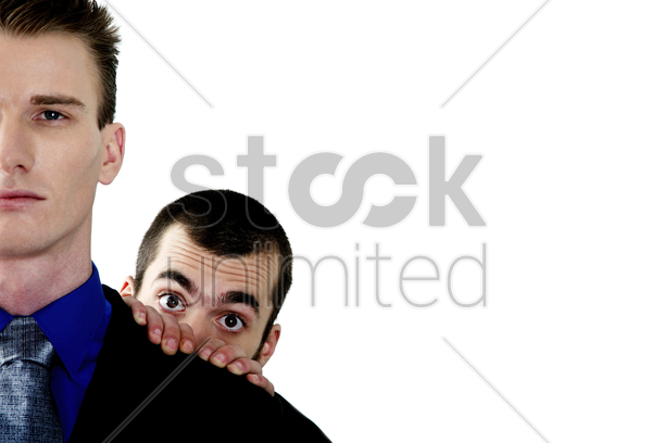 businessman hiding behind his colleague stock photo