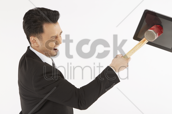 businessman hitting a digital tablet with hammer stock photo