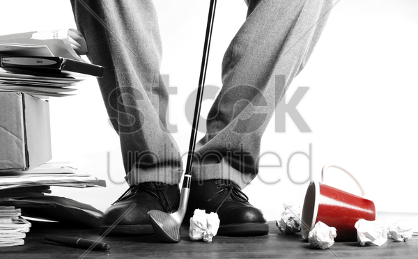 businessman hitting crumpled papers with golf club stock photo