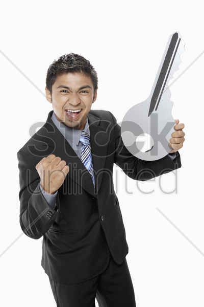 businessman holding a big key stock photo