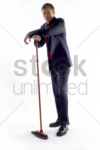 businessman holding a broom stock photo