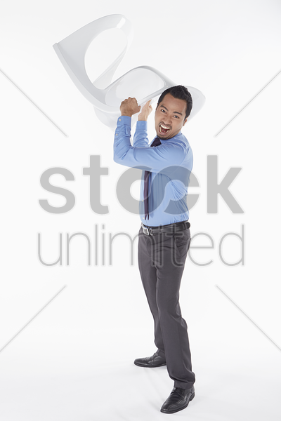 businessman holding a chair in anger stock photo