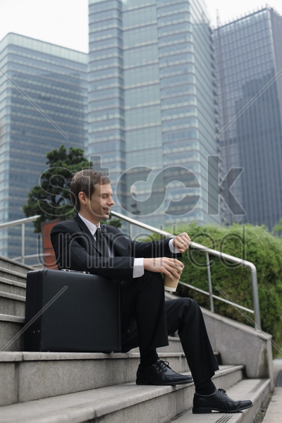 businessman holding a cup of coffee looking at his watch stock photo