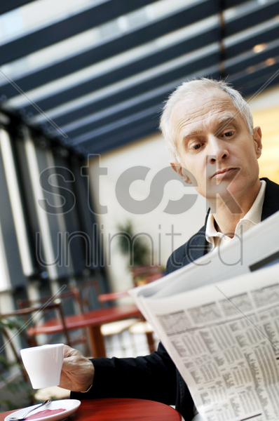 businessman holding a cup of coffee while reading newspaper in the cafe stock photo