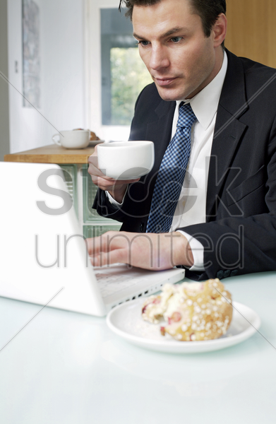 businessman holding a cup of coffee while using laptop stock photo