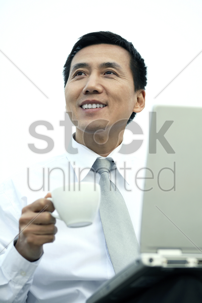 businessman holding a cup while using laptop stock photo