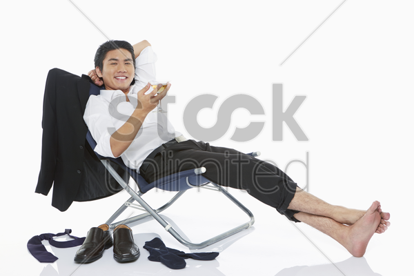 businessman holding a drink while lying on a chair stock photo