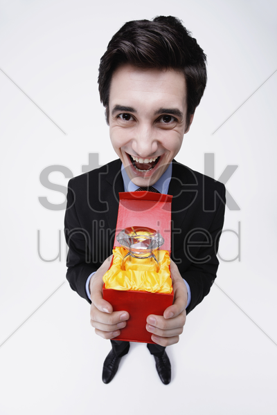 businessman holding a gigantic diamond ring in a box stock photo
