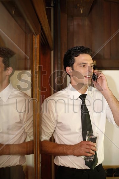 businessman holding a glass of water while talking on the phone stock photo