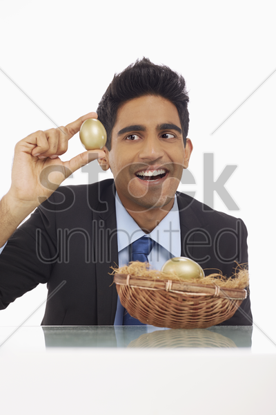 businessman holding a gold egg stock photo