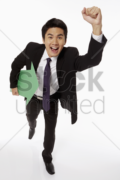 businessman holding a green arrow and running stock photo