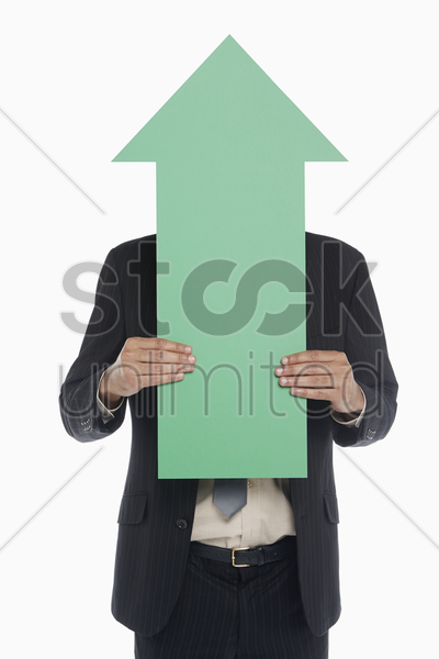 businessman holding a green arrow, covering his face stock photo