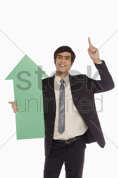 businessman holding a green arrow stock photo