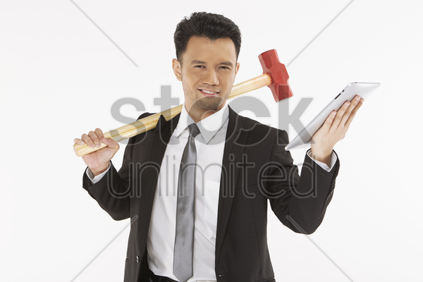 businessman holding a hammer and a digital tablet stock photo