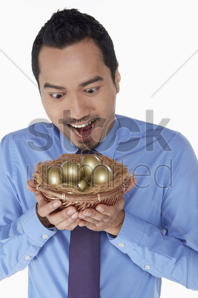 businessman holding a nest filled with golden eggs stock photo