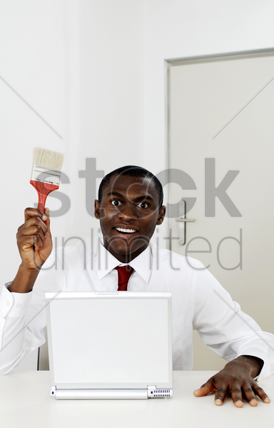 businessman holding a paint brush while sitting in front of the laptop stock photo