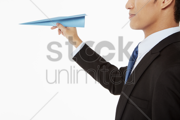 businessman holding a paper airplane stock photo