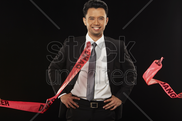 businessman holding a torn 'danger' tape stock photo