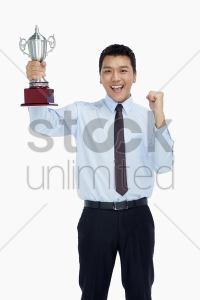 businessman holding a trophy and cheering stock photo