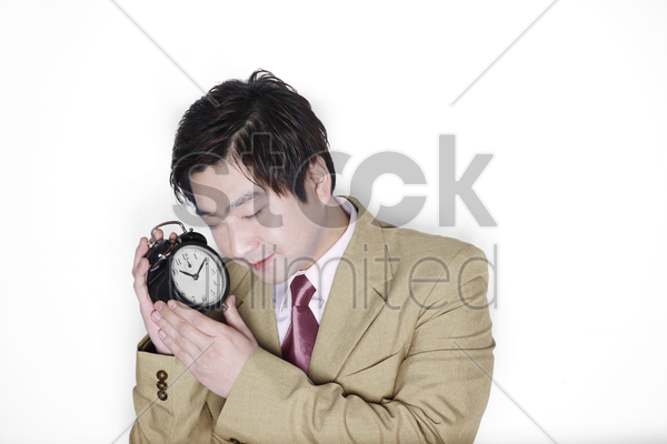 businessman holding an alarm clock while sleeping stock photo