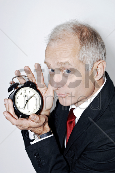 businessman holding an alarm clock stock photo