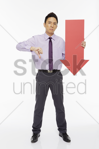 businessman holding an arrow, pointing downwards stock photo