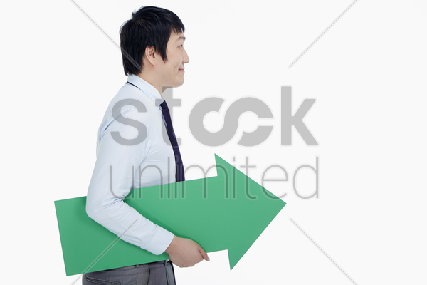 businessman holding an arrow, pointing to the left stock photo