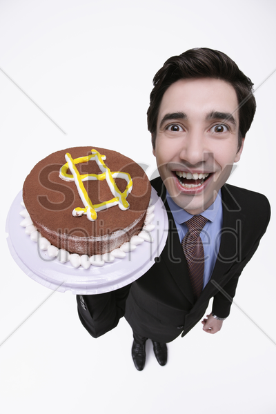 businessman holding cake with dollar sign stock photo