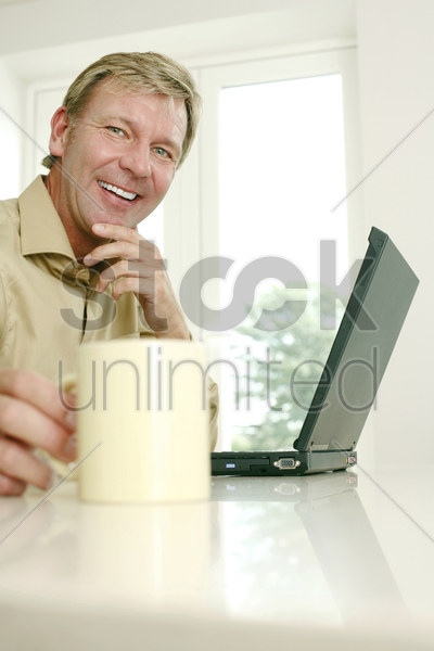 businessman holding cup while using laptop stock photo
