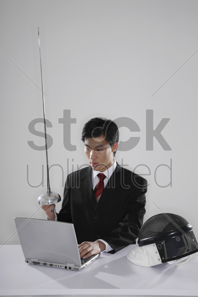 businessman holding fencing foil while using the laptop stock photo