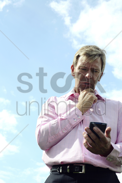 businessman holding his chin while looking at his pda stock photo